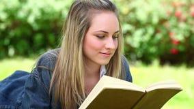 Mulher loura feliz que lê um livro video estoque