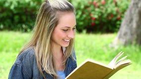 Mulher loura feliz que lê uma novela filme