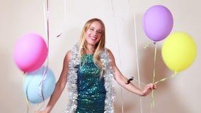Mulher loura feliz que salta com os balões na cabine da foto vídeos de arquivo