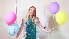 Mulher loura feliz que salta com os balões na cabine da foto video estoque
