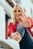 Mulher loura feliz que senta-se fora pondo sua mão perto da câmera imagens de stock royalty free