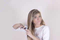 A mulher loura irritada corta seu cabelo com tesouras fotos de stock