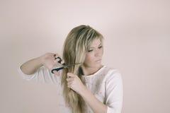 A mulher loura irritada corta seu cabelo com tesouras imagem de stock