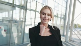 A mulher loura lindo em um equipamento preto olha direita para a câmera e compartilha de um sorriso bonito Terminal de aeroporto filme