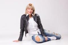 Mulher loura madura 40s que senta-se no assoalho Foto de Stock