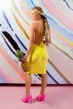 Mulher loura magro nova, bonito, bonita com tranças africanas e com os abacaxis em suas mãos Fotografia de Stock Royalty Free