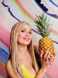 Mulher loura magro nova, bonito, bonita com tranças africanas e com os abacaxis em suas mãos Foto de Stock Royalty Free
