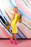 Mulher loura magro nova, bonito, bonita com tranças africanas e com os abacaxis em suas mãos Foto de Stock