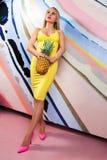 Mulher loura magro nova, bonito, bonita com tranças africanas e com os abacaxis em suas mãos Imagens de Stock Royalty Free
