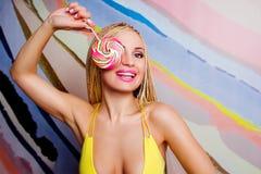 Mulher loura magro nova, bonito, bonita com tranças africanas e com pirulito Fotografia de Stock
