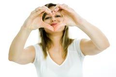 A mulher loura mostra a forma do coração com mãos - olhando através do coração imagem de stock