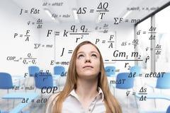 Mulher loura na classe com fórmulas Fotografia de Stock Royalty Free