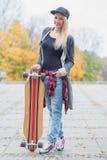 Mulher loura na moda lindo com uma placa do patim Foto de Stock
