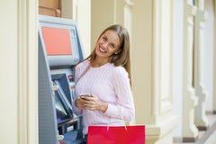 Mulher loura no fundo no shopping ATM imagem de stock royalty free