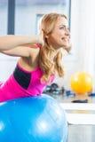 Mulher loura no sportswear que exercita com a bola da aptidão no gym foto de stock royalty free