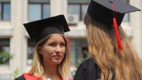 Mulher loura no tampão acadêmico que escuta o melhor amigo na cerimônia de graduação vídeos de arquivo