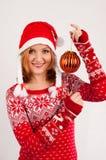 A mulher loura no tampão vermelho da camiseta do ` s do ano novo e do ` s do ano novo no fundo branco guarda a bola da árvore de  Foto de Stock