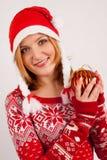 A mulher loura no tampão vermelho da camiseta do ` s do ano novo e do ` s do ano novo no fundo branco guarda a bola da árvore de  Imagens de Stock Royalty Free