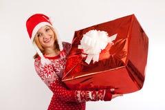 Mulher loura no tampão vermelho da camiseta do ` s do ano novo e do ` s do ano novo no presente grande das posses brancas do fund Imagens de Stock