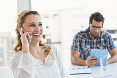 Mulher loura no telefone com seu colega atrás Fotos de Stock Royalty Free