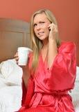 Mulher loura no telefone que guarda a veste vestindo do café Imagens de Stock Royalty Free