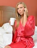 Mulher loura no telefone que guarda a veste vestindo do café Foto de Stock