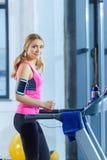 Mulher loura no treinamento do sportswear na escada rolante e no sorriso na câmera Imagem de Stock
