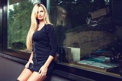Mulher loura no vestido curto preto que senta-se na soleira imagens de stock