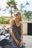 mulher loura nos óculos de sol que inclinam-se no velomotor foto de stock royalty free