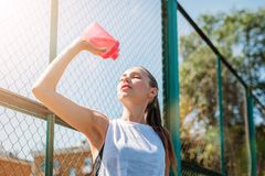 A mulher loura nova atlética bebe a água do copo dos esportes com água de iluminação fresca imagens de stock royalty free