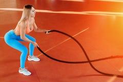 Mulher loura nova atlética que faz exercícios do crossfit com uma corda fotografia de stock royalty free