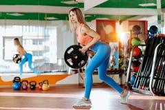 Mulher loura nova atlética que levanta com um disco do barbell no gym imagens de stock