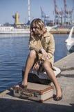 A mulher loura nova atrativa na trincheira com mala de viagem do vintage está sentando-se no cais de Jacht Foto de Stock