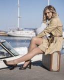 A mulher loura nova atrativa na trincheira com mala de viagem do vintage está sentando-se no cais de Jacht Fotografia de Stock