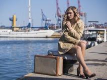 A mulher loura nova atrativa na trincheira com mala de viagem do vintage está sentando-se no cais de Jacht e está olhando-se no m Imagem de Stock Royalty Free