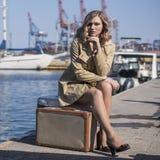 A mulher loura nova atrativa na trincheira com mala de viagem do vintage está sentando-se no cais de Jacht e está olhando-se no m Fotos de Stock