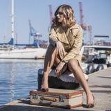 A mulher loura nova atrativa na trincheira com mala de viagem do vintage está sentando-se no cais de Jacht e está olhando-se no m Fotografia de Stock Royalty Free