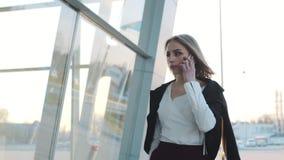 Mulher loura nova atrativa que puxa sua mala de viagem e que fala no telefone Equipamento à moda, vestuário formal Sendo ocupado video estoque