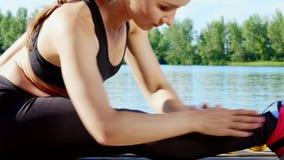Mulher loura nova bonita, atlética, treinador, instrutor, esticão, fazendo exercícios diferentes Lago, rio, céu azul vídeos de arquivo