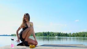 Mulher loura nova bonita, atlética, treinador, instrutor, esticão, fazendo exercícios diferentes Lago, rio, céu azul video estoque