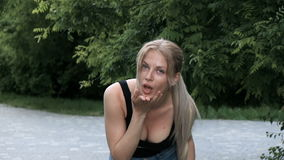 A mulher loura nova bonita com cabelo muito longo gerencie seu cabelo, faz um beijo do ar outdoor filme