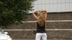 Mulher loura nova bonita com o cabelo longo que está para trás perto do carro branco a menina levanta a vista traseira Movimento  video estoque