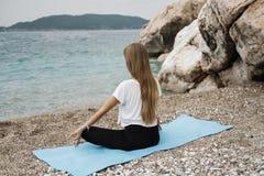 Mulher loura nova bonita com o cabelo longo que faz a ioga e o medita imagens de stock royalty free