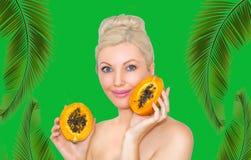 Mulher loura nova bonita com a papaia nas mãos O conceito da pele saudável e de hidratar Vantagens do fruto fotografia de stock royalty free