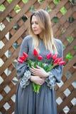 Mulher loura nova bonita com ramalhete das tulipas sobre na perspectiva de uma cerca de madeira Fotografia de Stock Royalty Free