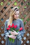 Mulher loura nova bonita com ramalhete das tulipas sobre na perspectiva de uma cerca de madeira Imagens de Stock