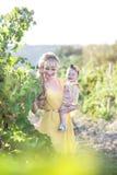 Mulher loura nova bonita com uma menina da criança no campo de g Imagem de Stock
