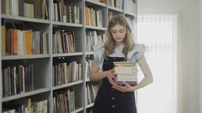 Mulher loura nova bonita do estudante que anda na biblioteca da universidade com muitos livros nas mãos filme