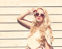 Mulher loura nova bonita do retrato sensual exterior da forma do verão um vestido branco que está no fundo de pranchas de madeira imagens de stock royalty free
