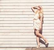 Mulher loura nova bonita do retrato sensual exterior da forma do verão um vestido branco que está no fundo de pranchas de madeira Imagem de Stock